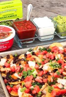 Easy Oven Nachos on a cookie sheet with sour cream, salsa, and guacamole in the background.