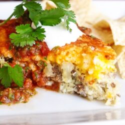 Easy Taco Pie topped with sour cream, salsa, and cilantro with chips in the background.
