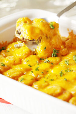 Tater tot casserole in baking dish with ground beef, green beans, tater tots, and cheese