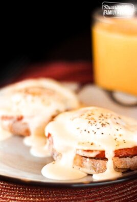 Foolproof Eggs Benedict on a plate with orange juice in the background.
