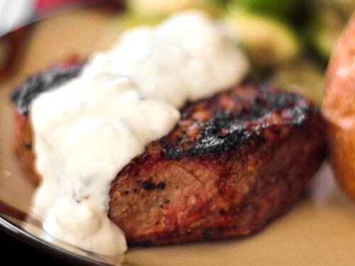 Filet Mignon topped with Melted Blue Cheese Sauce on a tan plate.