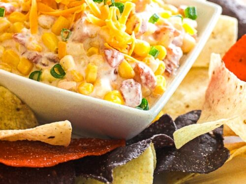 Creamy Corn dip in a square white bowl with tortilla chips on the side