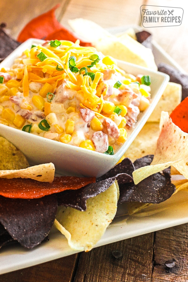 Easy Creamy Corn Dip topped with cheese in a white class bowl surrounded by tortilla chips.