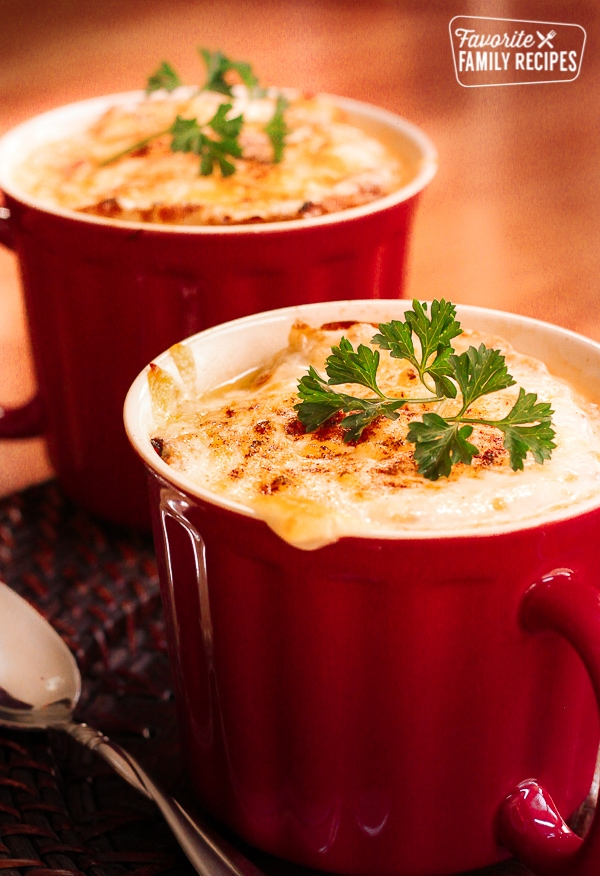 French Onion Soup in a red mug topped with a garnish.