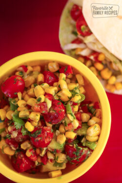 Fresh Corn Salsa in a yellow bowl with tortillas in the background.