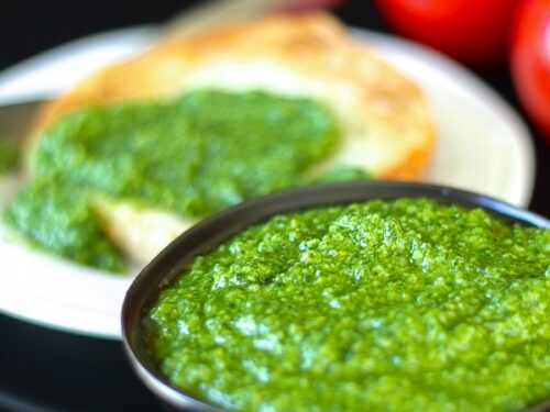 Fresh Homemade Basil Pesto in a black bowl with more pesto and tomatoes in the background.