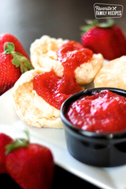 Fresh and Easy Strawberry Jam in a small black bowl with rolls and jam on the side on a white plate surrounded by strawberries.