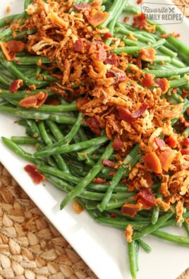 Fresh green beans on a white platter topped with bacon bits and onion straws