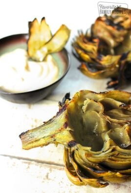 Grilled Artichokes with a side of lemon mayo dip in the background.
