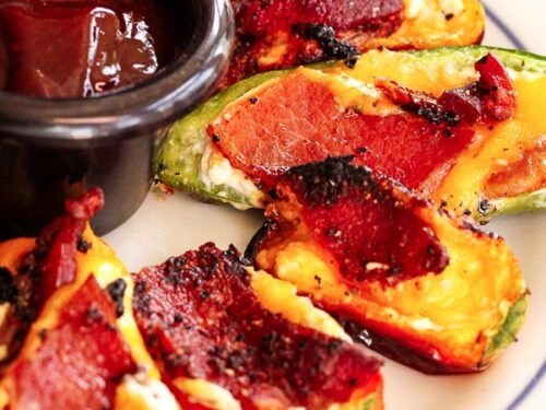 Grilled Cheesy Bacon Jalapenos surrounding a small black bowl with sauce on a white plate.