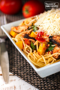 Grilled Chicken Pasta Primavera topped with cheese in a white bowl.