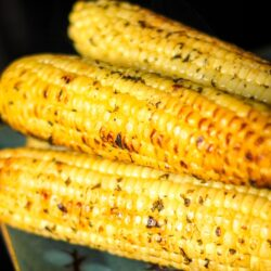 Grilled Cilantro Lime Corn on the Cob stacked on top of each other on a plate.