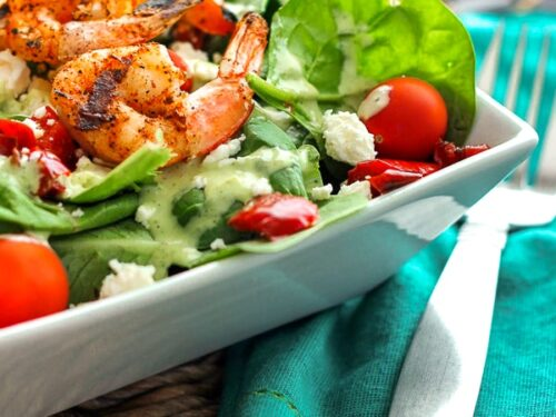 Grilled Shrimp Salad with Cilantro Verde Dressing in a white bowl with a fork on the side.