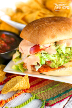 Guacamole Chicken Torta Sandwich on a white plate with chips and salsa on the side.