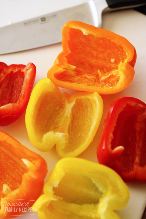 Red, yellow, and orange bell peppers sliced on a cutting board