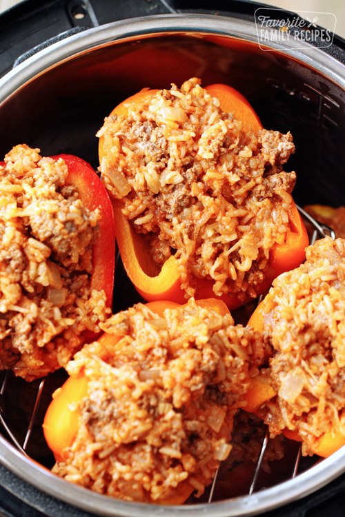 Uncooked stuffed bell peppers layered in an Instant Pot