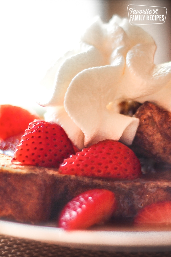 Close up of Kneaders French Toast topped with strawberries, whipped cream, and Caramel Syrup
