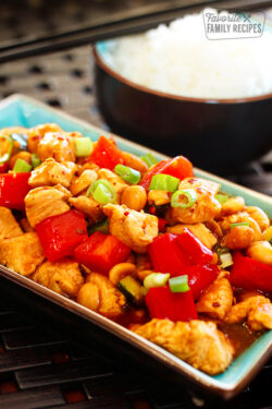 Kung Pao Chicken on a blue tray with a side of white rice in the background.