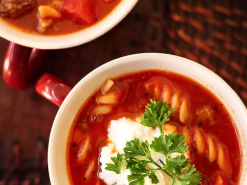 2 white bowls of Lasagna Soup topped with cheese and a garnish
