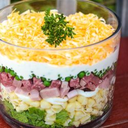Layered Pasta Salad with ham, peas, noodles in a glass dish topped with cheese and a garnsih.