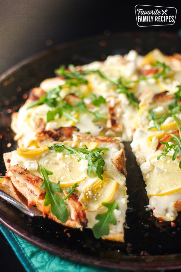 Lemon Chicken Pizza with a slice poking out on a pizza pan
