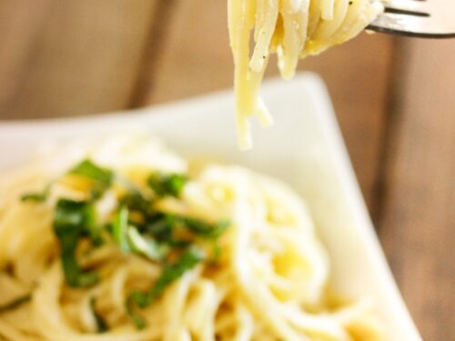 Fresh and Easy Lemon Spaghetti in a bowl with a fork in focus with noodles swirled around it.