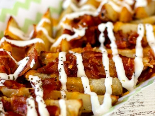 Loaded Potato Wedges on a tray drizzled with ranch.