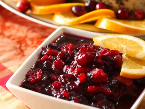Low Sugar Cranberry Sauce topped with ornage slices in a white Serving Dish