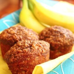 Lowfat Banana Crumb Muffins on a yellow and blue cloth with bananas in the background.