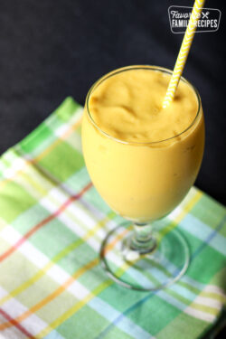 Mango Avocado Smoothie in a Glass on a plaid cloth.