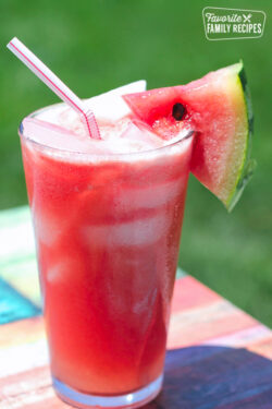 A glass of Melonade with a straw and watermelon slice.