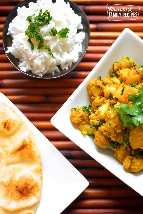 Curried Cauliflower and Potatoes in a Dish with Naan Bread on the side