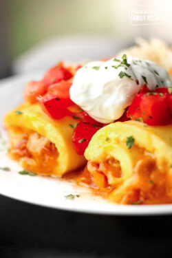 Omelette Roll Ups topped with sour cream and tomatoes on a white plate.