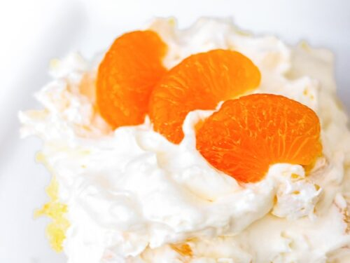A slice of Orange Pineapple Cake topped with mandarin oranges on a white plate.
