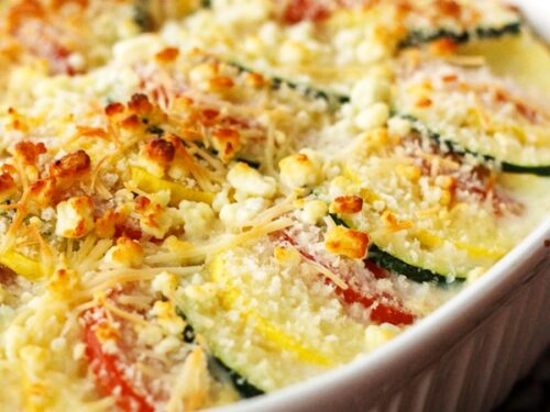 Parmesan Squash Casserole with layers of sliced squash and zucchini in a white ceramic baking dish