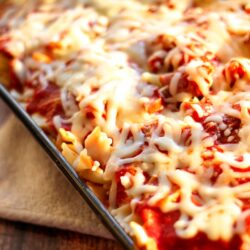 Pasta Sausage Bake topped with melted cheese in a glass pan