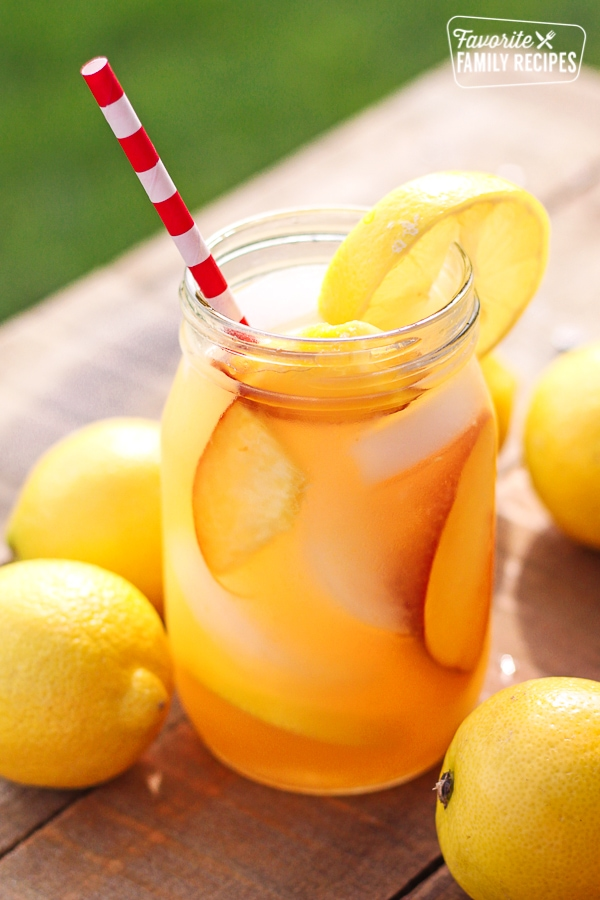 Easy Peach Lemonade in a mason jar with a red and white striped straw sticking out.