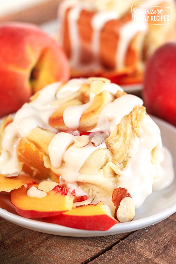 Peaches and Cream Cinnamon Roll with a couple peach slices on the side on a white plate.