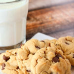 A plate of peanut butter chocolate chip cookies with a glass of milk to the side