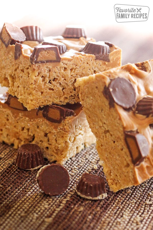 Peanut Butter Cup Rice Krispie Treats stacked on top of each other with peanut butter cups on the side.