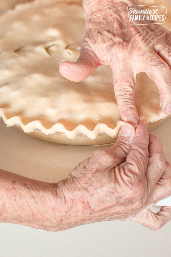 Pie crusts being pressed together with fingers