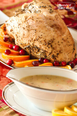 A Roast Turkey Breast served on a platter with orange slices and lemon rosemary gravy on the side