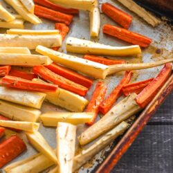 Roasted parsnip and carrot sticks on a baking sheet