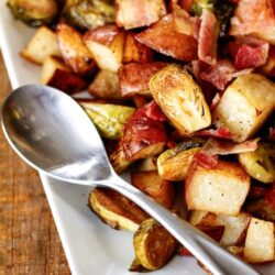 white plate with roasted potatoes and brussels sprouts and silver spoon