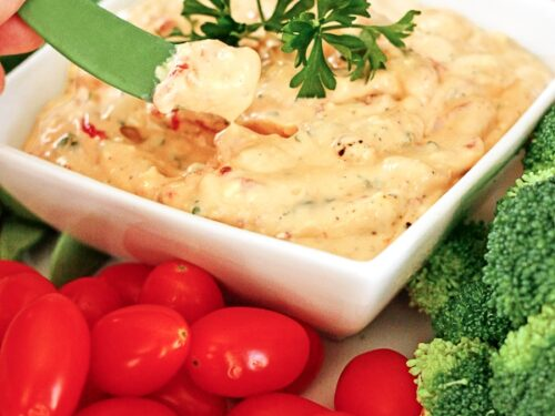 Roasted Red Pepper Dip in a dish surrounded by veggies.