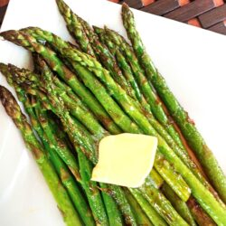 Sautéed Sweet Asparagus on a plate with a square of butter melting on top