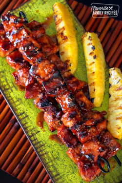 Pork Kabobs on a serving platter with pineapple