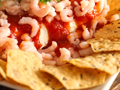 Shrimp and cocktail sauce over cream cheese served with tortilla chips