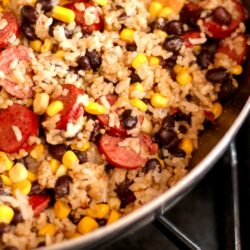 A skillet filled with sausage and rice with black beans and corn