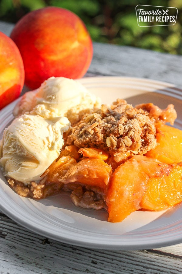 Crock Pot Peach Cobbler served with two scoops of vanilla ice cream with fresh peaches in the background